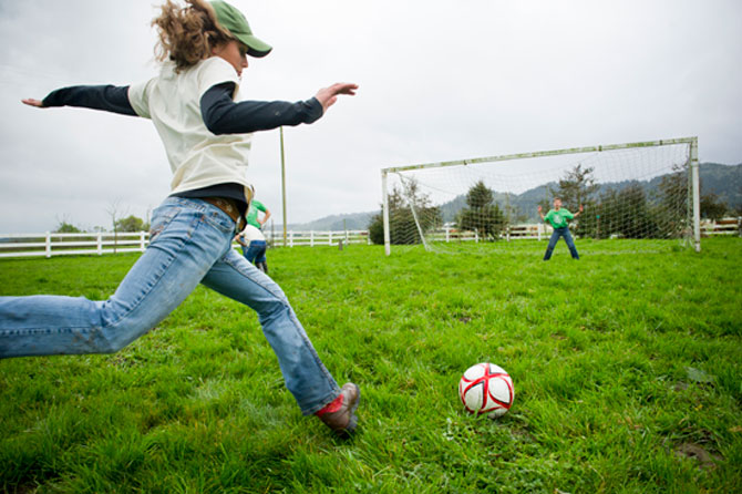 Girl kicking soccer ball